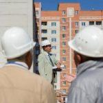 men in hardhats standing in front of building